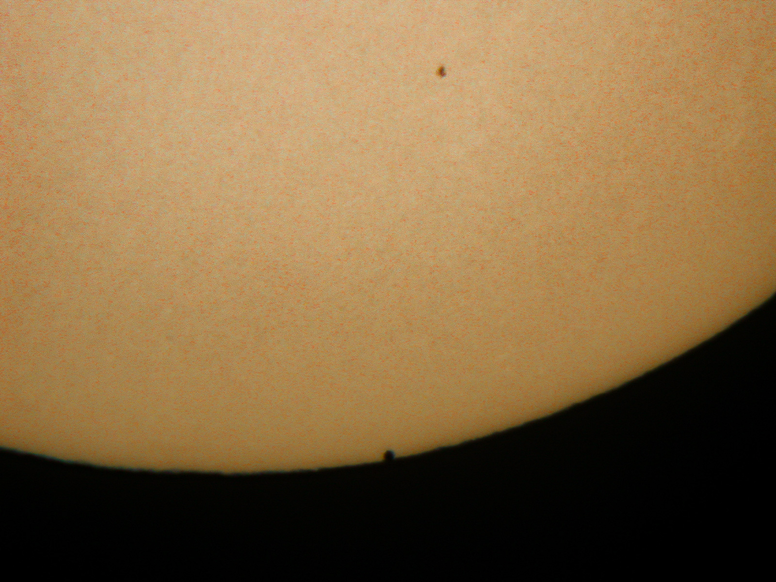 The disc of mercury starts to become visible against the sun.